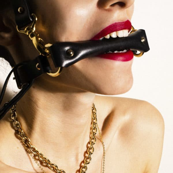 Gag head harness in black leather from Elif Domanic. A strap placed at the level of the mouth is maintained by two golden rings to another strap which is placed at the back of the skull. Another strap much longer is attached to the whole by a loop and loops.