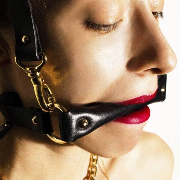 Arnés para la cabeza en cuero negro de Elif Domanic. Una correa colocada a la altura de la boca se mantiene mediante dos anillos dorados a otra correa que se coloca en la parte posterior del cráneo. Otra correa mucho más larga está unida al conjunto por un lazo y unas presillas.