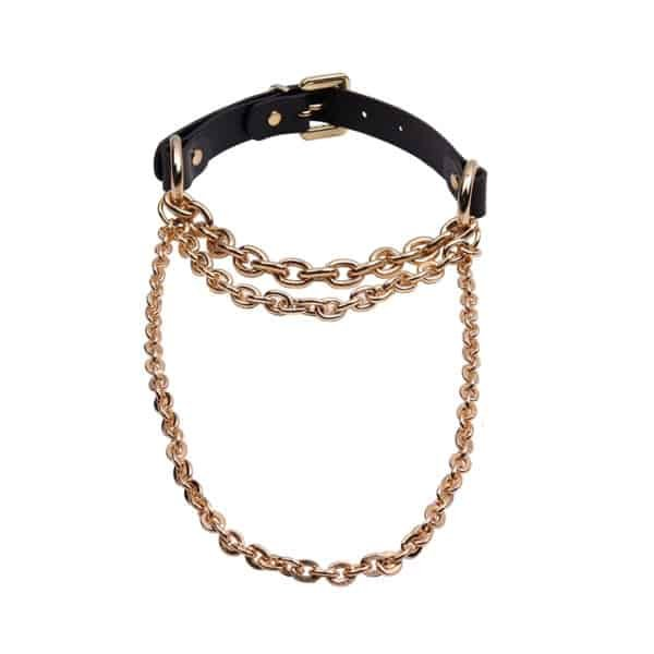 Choker Bondage of the brand Elif Domanic. This choker is composed of a thick black leather collar with a thick gold buckle as a closure, two rings hold three gold chains that form the necklace of the product and are of different thicknesses and heights.