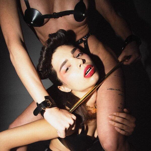 Cache tétons noir de la marque Elif Domanic. Un harnais conçu de lanières en cuir noir maintient les caches tétons et s'attache à l'aide de fines boucles argentées au niveau du thorax ou du milieu du dos. Les bretelles de ce harnais sont également réglables. Les caches tétons sont en cuir noir avec au sommet de chaque un accessoire pendant doré. A l'intérieur de la bretelle de droite se trouve une plaquette dorée embossée du nom de la marque.