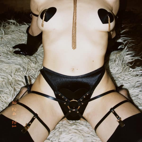 Harness suspender belt from Elif Domanic. This harness is composed of leather straps and gold-coloured rings, adjustments and nails. At the level of the intimate parts, there is a heart-shaped piece of black leather with a ring in the middle that connects all the straps of the harness that are placed on the hips, pelvis and thighs.