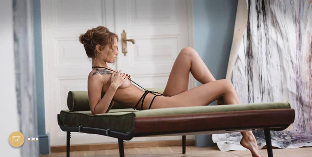 Playsuits Scarlett de la marque Couture de nuit inspirés du bondage. Le produit est confectionné d'élastiques en velours noir et de curseurs et anneaux en plaqué or. Un anneau central est placé au niveau du nombril et regroupe les huit élastiques placés de part et d'autres des hanches ainsi que deux autres partant du cou, vers le creux des seins et jusqu'à cet anneau. Le produit s'attache au cou laissant le dos et les cuisses nus.