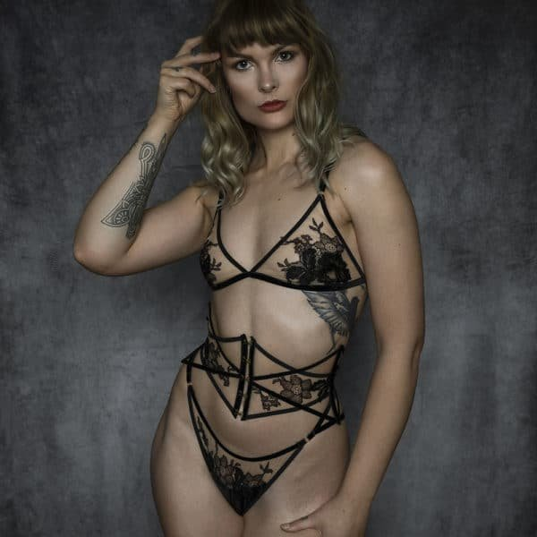 Lingerie set from the brand HERVÉ by Céline Marie with a triangle bra and suspender belts whose shape is ensured by black velvet elastics and a transparent fabric decorated with black lace. The clasps of the garter belts and bra rings are golden. A waist corset is also present with black velvet elastic lacing and five gold brass ties. Very fine lace overhangs this corset on the central and horizontal part of it.