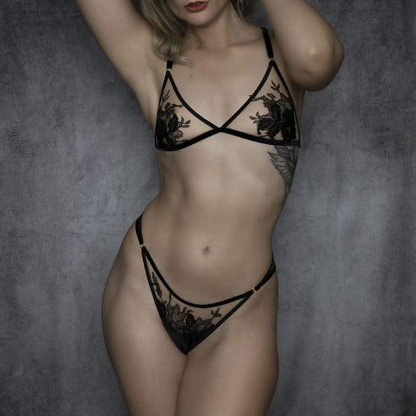 Lingerie set from the brand HERVÉ by Céline Marie with a triangle bra and suspender belts whose shape is ensured by black velvet elastics and a transparent fabric decorated with black lace. The clasps of the garter belts and bra rings are golden.