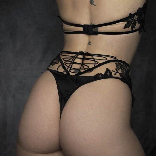 Ensemble de lingerie collection syntosis de la marque HERVÉ by Céline Marie. Le soutien gorge intégral a une forme est assurée par des élastiques de velours noir et un tissu transparent orné de dentelle noire. Le coin extérieur de chacun des bonnets est renforcé d'un tissu noir. Les anneaux du soutien gorge sont de couleur dorée. La culotte est une taille haute simple des mêmes compositions de tissus avec un laçage ajustable dans le bas du dos.
