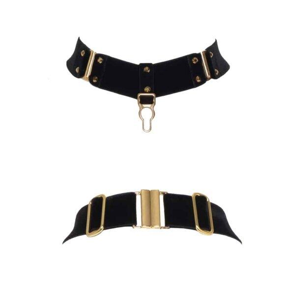 Collier Verene noir de la marque Hervé by Celine Marie. Ce collier est confectionné à partir d'un élastique noir en velours doux épais et de réglages et crochets en plaqué or 24 carats. Un fermoir doré est placé en guise de pendentif, à ses cotés se présentent deux crochets encadrés de clous. A l'arrière, Un fermoir et de réglages sont présents.
