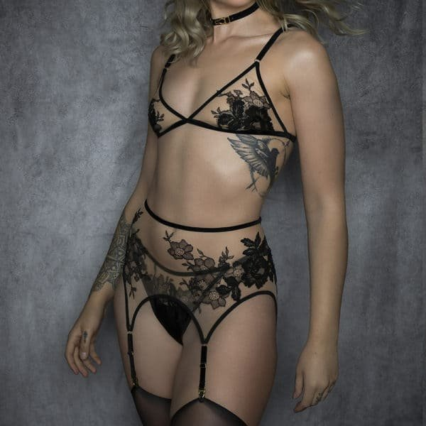 Lingerie set from the YVEA collection by HERVÉ by Céline Marie with a triangle bralette and garter belts shaped with black velvet elastics and a transparent fabric decorated with black lace. The clasps of the garter belts and bra rings are gold-coloured.