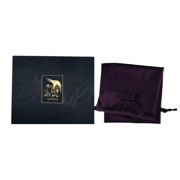 Packaging of the bondage belt of the brand UPKO, it is about a purple velvet pouch with the inscription UPKO of black color. The box of this pouch is composed of a background with black and silver foliage patterns with a central square that displays the inscription and the logo of the UPKO brand in a golden color.