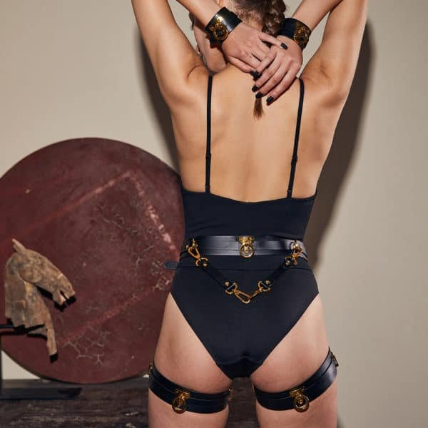 Set composed of handcuffs, leg loops and a black bondage belt from UPKO, to attach your bdsm accessories. The black leather of each product is also equipped with gold brass rings and slides.