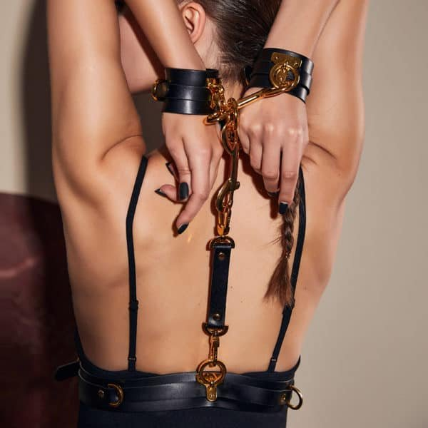 Set composed of handcuffs as well as a black bondage belt from UPKO, the two elements are linked by carabiners keeping your upper limbs in your back. The black leather of each product is also equipped with gold brass rings and slides.