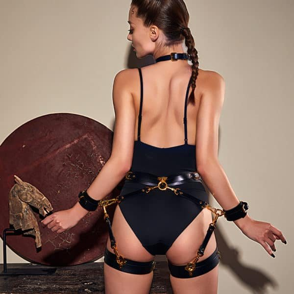 Set composed of a choker, leg cuffs and a black bondage belt from UPKO, the last three elements are linked by carabiners keeping your limbs in your back. The black leather of each product is also equipped with gold brass rings and slides.