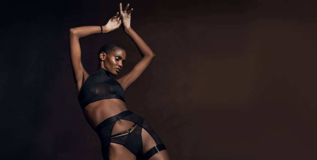 The model is wearing a Rey set from the brand Bordelle composed of a Navy Blue Crop Top with a sleeveless turtleneck, open at the back and adjustable with two golden buckles at the back, a Navy Blue Suspender Belt with a transparent side panel and a Navy Blue Thong adjustable with golden buckles at the sides.