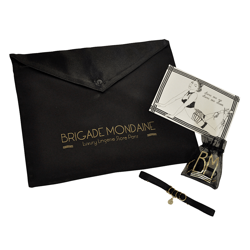 Gift Pack Brigade Mondaine composed of a black satin envelope with the inscriptions of the Brigade Mondaine in gold. This envelope is useful to wrap the product. The pack also includes a personalized card and a Brigade Mondaine choker with its gift bag. Ideal for a woman gift