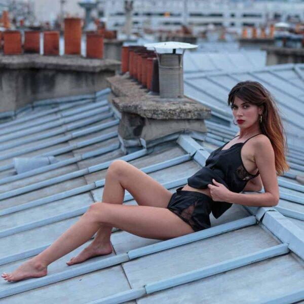 Модель одета в черный атласный топ из коллекции Nuit à Broadway от Atelier Amour. Спереди имеется V-образный вырез.