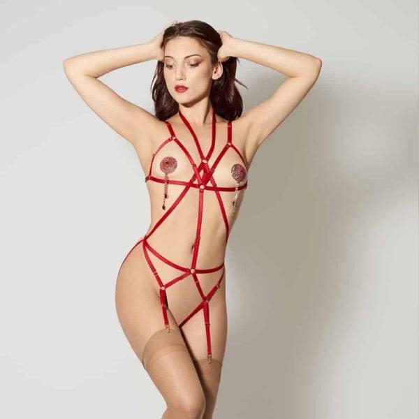 Signature Playsuit Bondage Rouge de la marque ELF ZHOU LONDON. La pièce est ouverte au niveau des seins et passe autour du cou pour longer dans le sens de la longueur le haut du corps. Il y a une bande centrale de couleur rouage et deux bandes rouge qui passent en diagonal de part et d'autre. Au niveau de la ceinture passe une bande rouge, elle-même reliée à deux bandes rouge qui longent de manière diagonale le haut des cuisses. Elle porte des collants couleur chair qui arrivent jusqu'en haut de ses cuisses. Elle a également des nippies argentées rouges avec des strass.