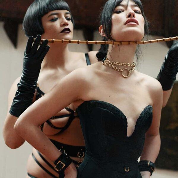 La modelo lleva el collar O Chain de The Model Traitor. En la parte delantera se puede ver una cadena doble, una más baja que la otra, con un anillo en forma de O. En la parte posterior, el collar se cierra con una hebilla de cinturón de latón dorado y piel de vaca.