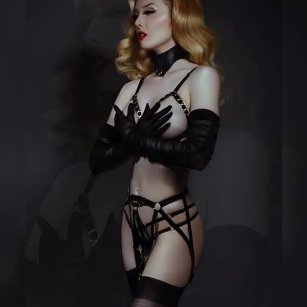 The model is wearing the Simone Open Bra from THE MODEL TRAITOR. This model is completely open and reveals the whole chest. The breasts are maintained by bands of satin elastic. They are arranged in the form of a triangle. The bottom band is simply black. But those of the top are black and covered with gold-plated brass. The straps are also satin elastic and have a small gold-plated detail to adjust them.