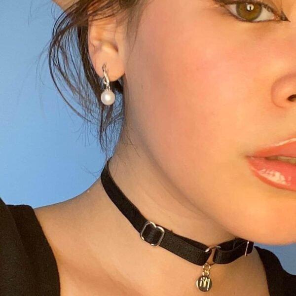 Collier BM inclut dans le pack cadeau Brigade Mondaine. Le produit est un choker simple avec un tour de cou en élastique noir et un pendentif doré embossé du logo Brigade Mondaine. Ce bijoux est attaché au collier par un anneau. L'ensemble du produit est réglable.