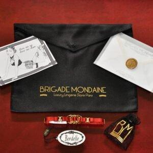Photo du pack cadeau rouge Bordelle et Brigade Mondaine. On peut y voir un collier Bordelle rouge fait d'élastique et de détail rond en doré.