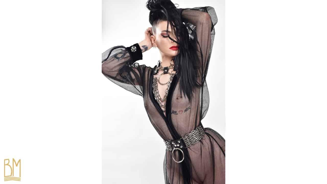 Sesión fotográfica de Lada Vesna photography en colaboración con Brigade Mondaine con la modelo Julie Von Trash que lleva la marca Upko. El Kimono Bijoux et Résille negro está hecho de malla y tiene joyas como gemelos. Viene con un cinturón de tela en la cintura.