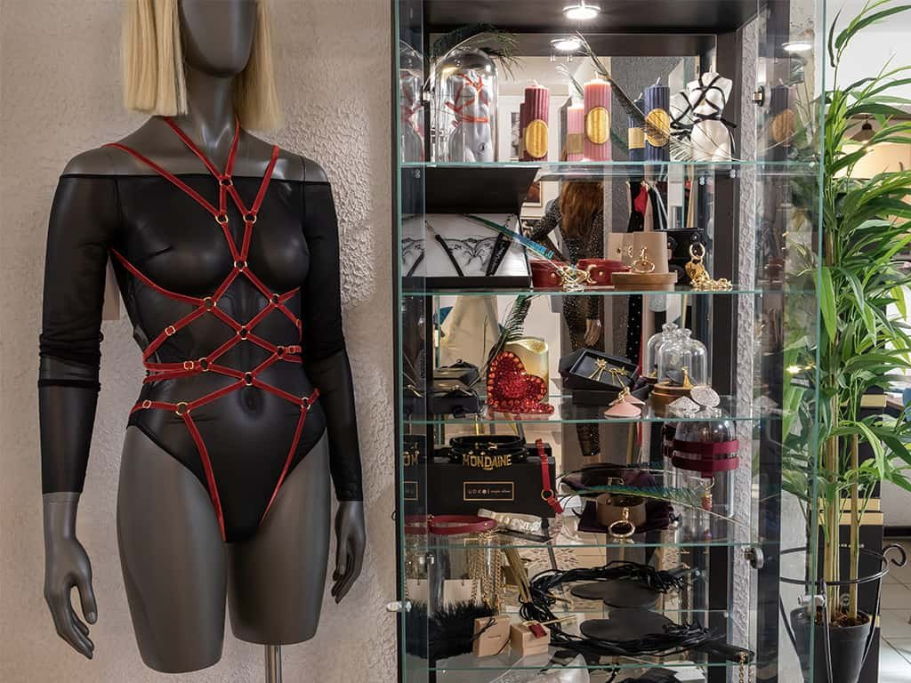 We can see a showcase filled with different BDSM accessories, and candles. On the left side of the window a model is wearing a black mesh bodysuit from Zhilyova and a Couture de Nuit playsuit made of thin red elastic.