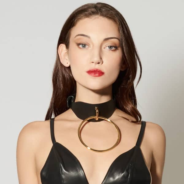 Leather Artefact Chocker O Noir de la marque ELF ZHOU LONDON. Le chocker est cuir noir et possède au centre de celui-ci une grosse boucle en or. Le modèle porte un soutien triangle noir cuir.