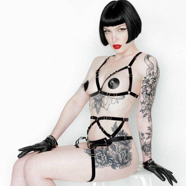 Leather Artefact Nippies Ring Bondage Noir de la marque ELF ZHOU LONDON. Avec cela le modèle porte un soutien triangle en cuir ouvert sur les seins. Elle porte au niveau du bas un harnais noir qui débute du milieu de son ventre avec une bande noir qui passe de manière horizontale et finit au niveau de ces cuisses. Le modèle porte des gants en cuir. Elle a beaucoup de tatouages fleuris. Elle est assise sur un tabouret blanc et regarde l'objectif.