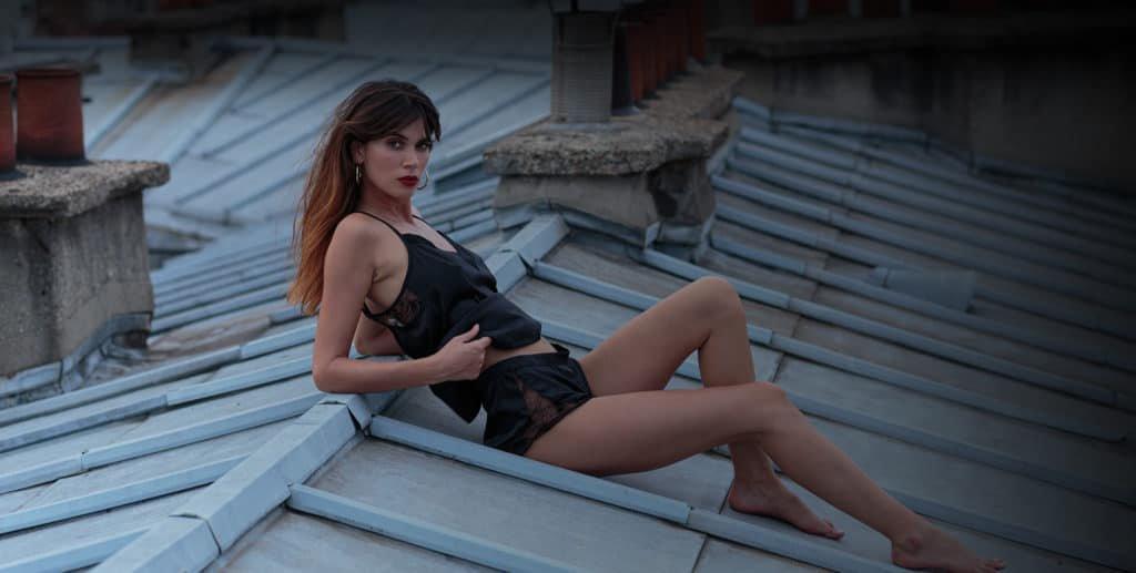 Le mannequin porte un pyjama Atelier Amour composé d'un haut en satin et dentelle noir. Ainsi qu'un shorty en satin et dentelle noir. La mannequin pose sur un toit parisien.