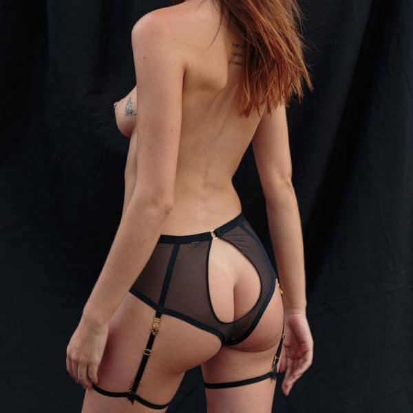 The model is wearing the Harness panty from Atelier Amour, it is made of tulle and black satin elastic. The harness starts from the neck, goes through the panties and ends in a garter on the model's thighs. We can see an opening in the center.