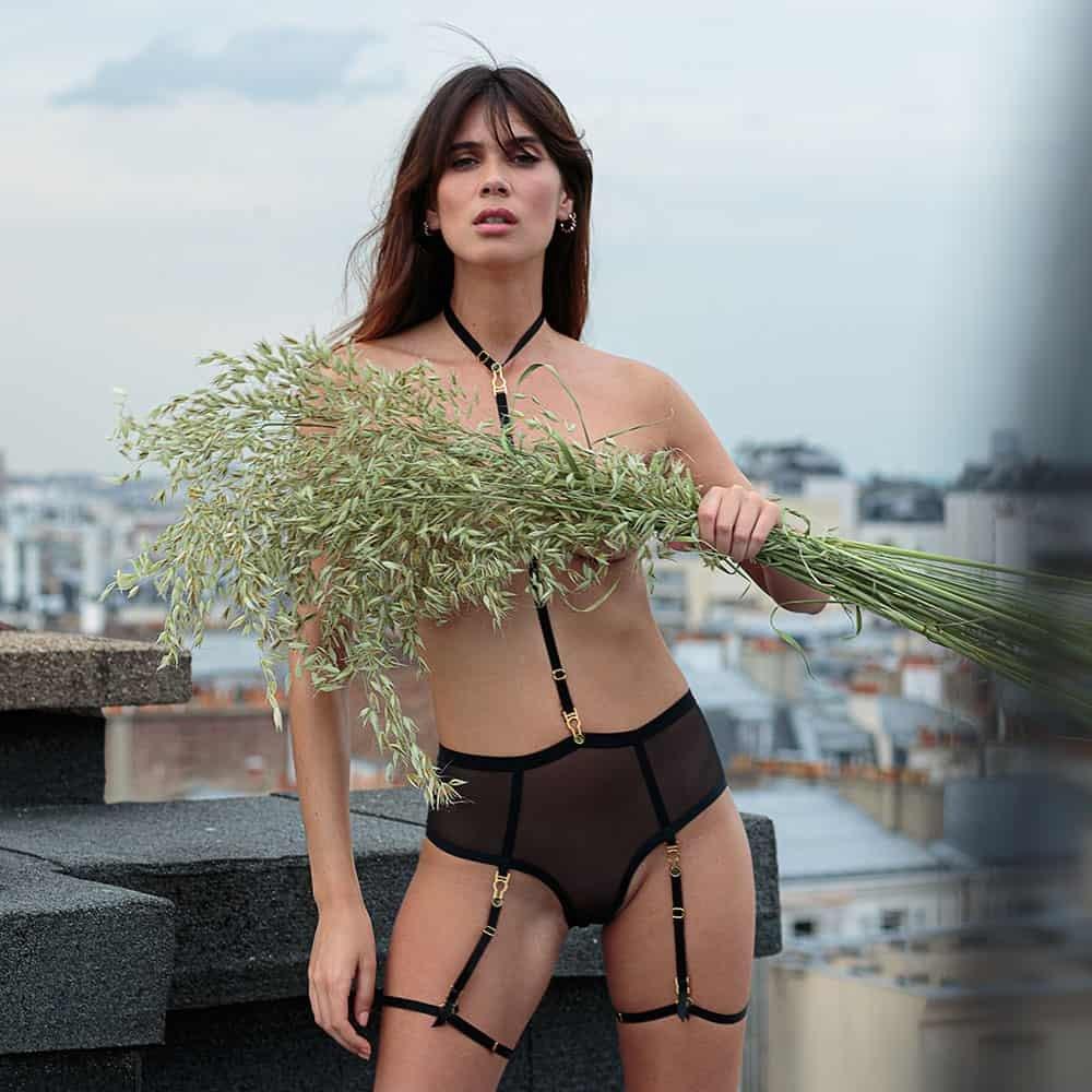 На модели трусики Unbearable Lightness Harness от Atelier Amour, выполненные из тюля и черной атласной резинки. Жгут начинается от шеи, проходит через трусики и заканчивается подвязкой на бедрах модели.