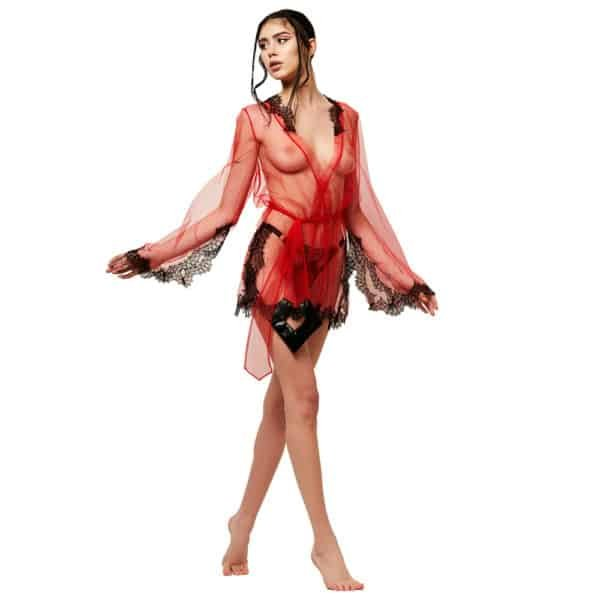 На модели красное короткое кимоно от LUDIQUE LINGERIE. Воротник, рукава и низ украшены черными кружевными деталями. Также имеется красный пояс, обозначающий талию.