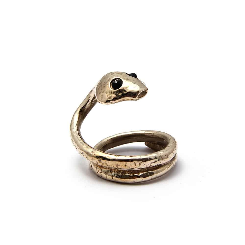 Ceci est une bague en forme de serpent. Le serpent a pour yeux des pierres noires. La queue du serpent s'enroule afin de former un anneau large.
