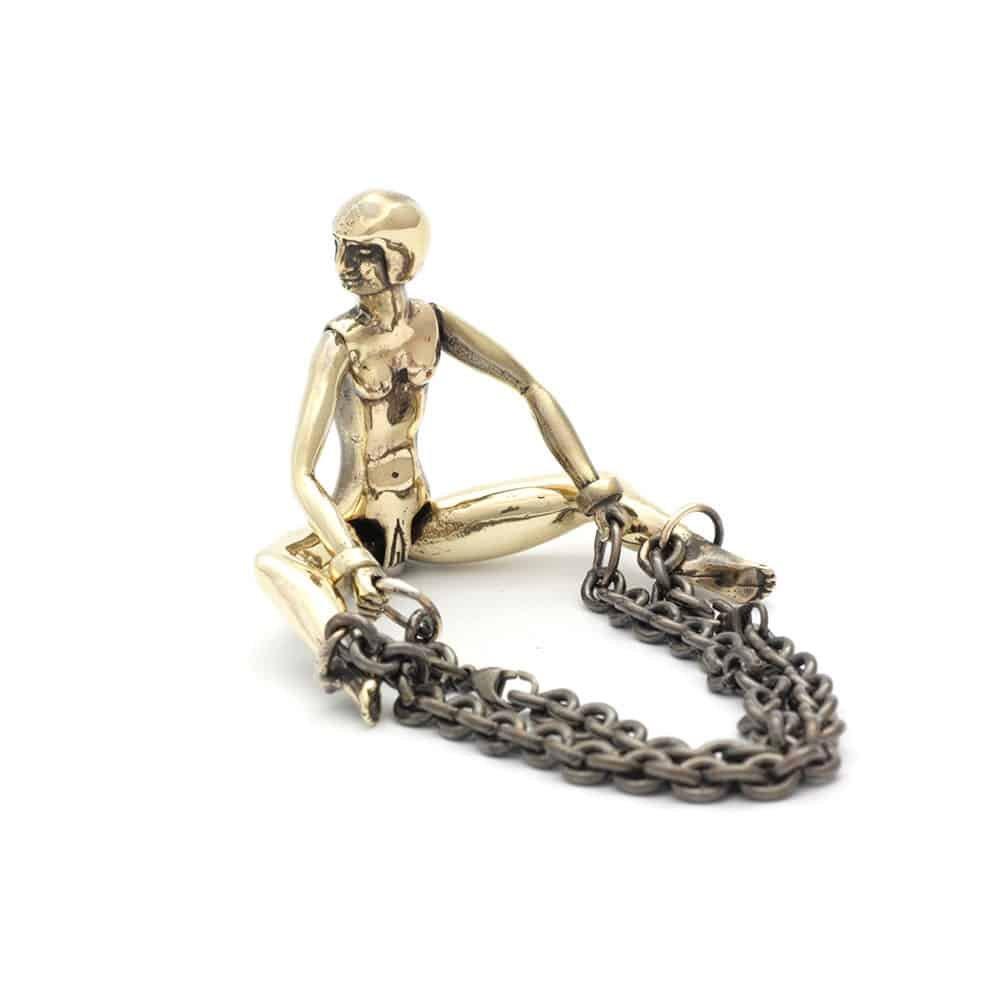 Ceci est un cockring en forme de poupée en bronze patiné. Tout en tournant la tête du côté droit, elle écarte les jambes et elle a des chaînes aux pieds.
