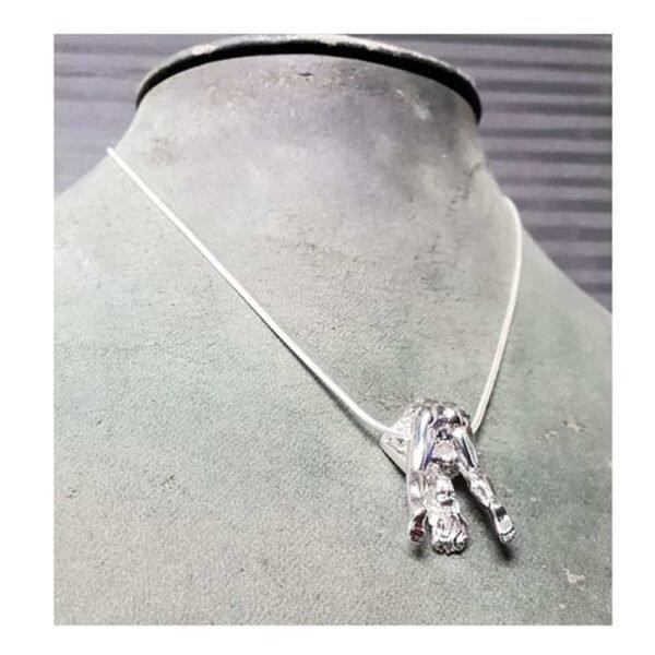 Collar de plata Rosebuds, teniendo una mujer de plata que nos muestra su anatomía, de hecho tiene las piernas en el aire abiertas.