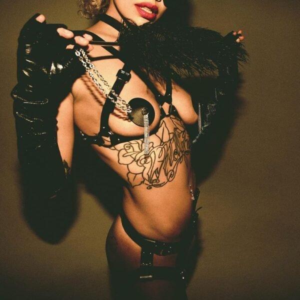 Ceinture Electra Elif Domanic harnais de bondage en cuir de couleur noir. Au niveau du nombril, un boucle avec des trous réglables orne la ceinture. Deux passants permettent de tenir aux cotés les jarretelles qui elles aussi sont en cuir et réglable.