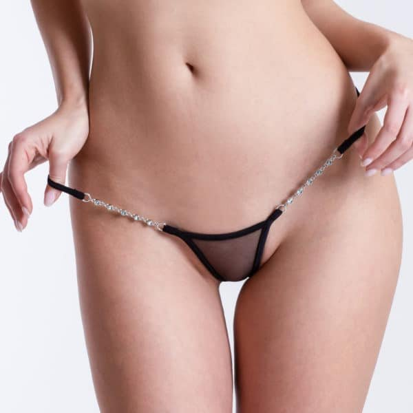 Here you can see the Micro V thong Transparent Black from the brand LUCKY CHEEKS. In front, the crotch is covered by transparent black tulle. The chains on the hips are made of zamac jewelry.
