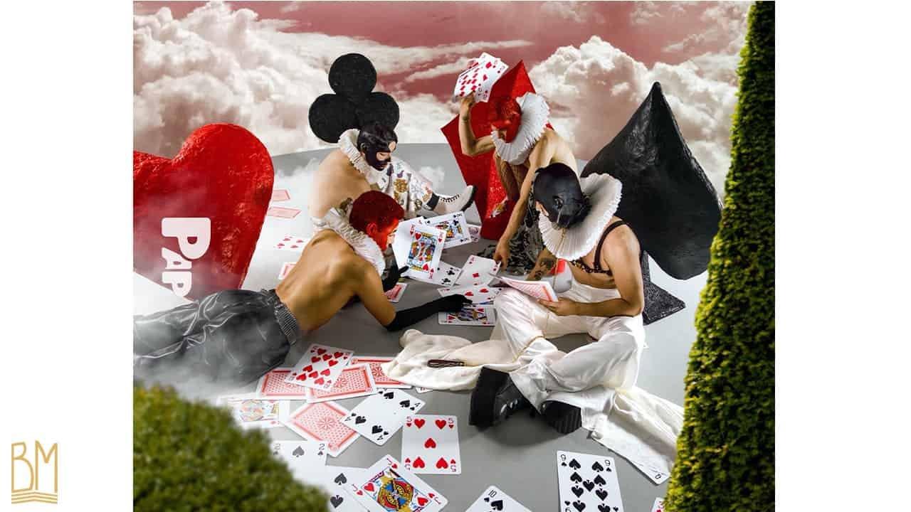PAP Magazine avec 4 hommes dont trois hommes assis et un couché sur le sol. Deux d'entre eux ont le visage en noir et les deux autres en rouge. L'homme tout à droite porte une laisse de la marque Upko. Ils sont en train de jouer aux cartes. Derrière eux se trouvent le signe du coeur, du pique et du carreau. Sur le sol, sont éparpillées des cartes. Derrière eux, on peut apercevoir des nuages et le ciel.
