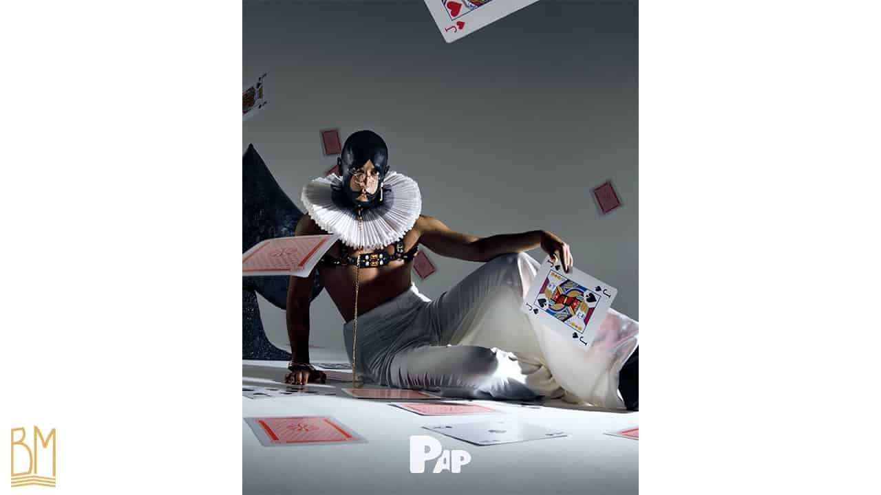 PAP Magazine il s'agit d'un homme portant une laisse de la marque Upko. Son visage est peint en noir et forme le signe du pique. Il tient dans sa main une carte valet de pique. Des cartes tombent derrière lui et d'autres cartes sont éparpillées sur le sol.