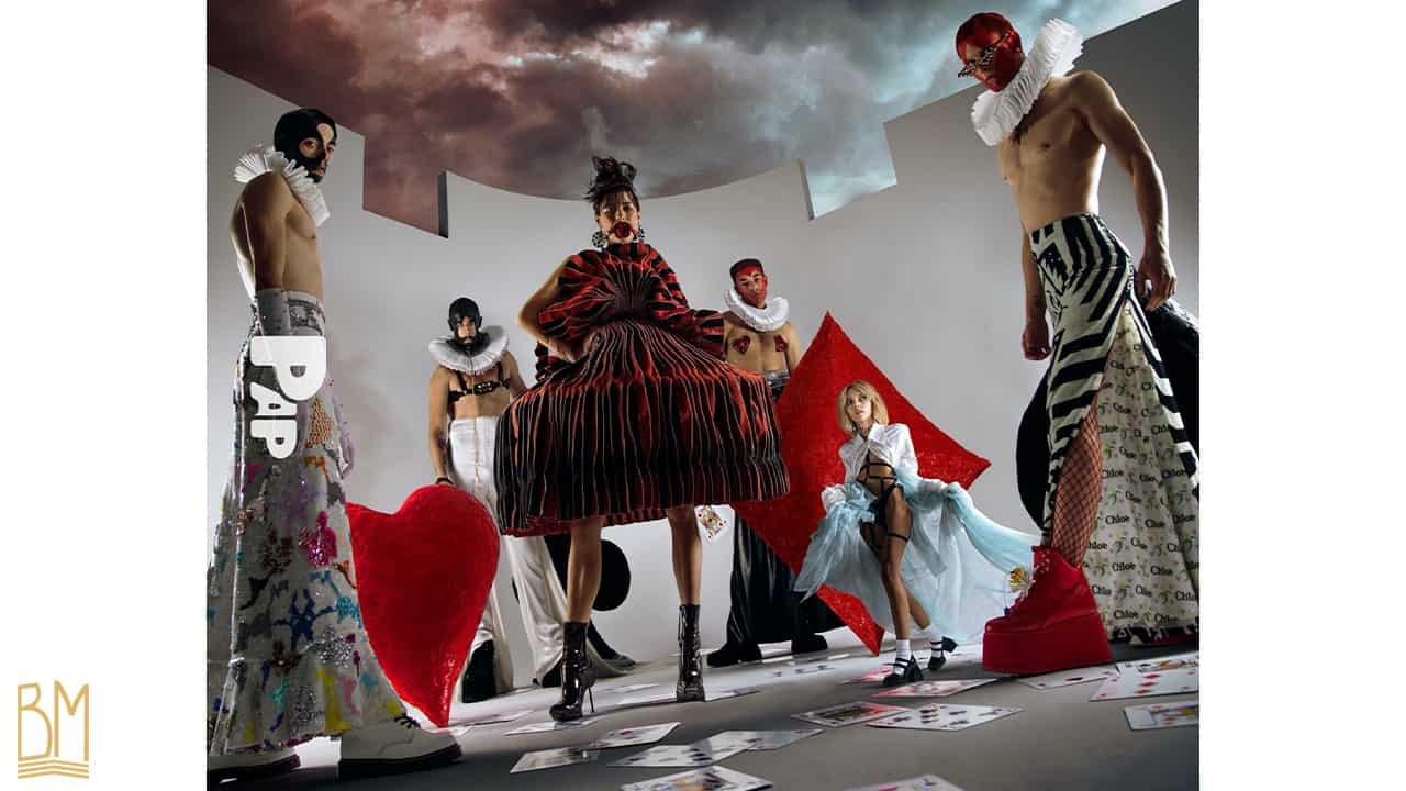 PAP Magazine il y a 4 hommes vêtus en noir, rouge et blanc positionnés autour de deux femmes. Le deuxième homme à gauche porte une laisse Upko. L'homme à sa droite porte les nipples de la marque Ruth Melbourne. À côté d'eux, se trouvent le signe du coeur rouge, le signe du trèfle noir et le signe du carreau rouge. Quant aux femmes, il y en a une grande vêtue d'une robe rouge et noires, elle porte le Ball Gag de la marque Upko et à côté d'elle une plus petite femme portant un harnais et par dessus une cape longue blanche.