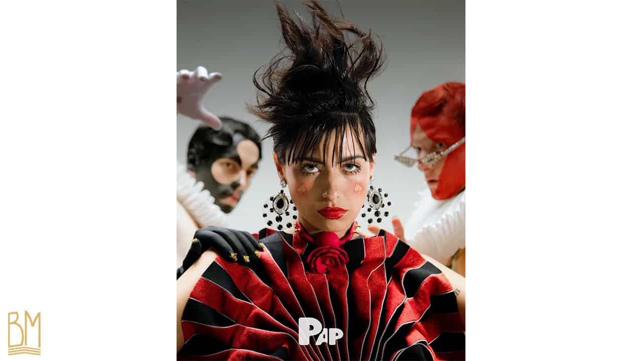 PAP Magazine il s'agit d'une femme portant autour de son cou elle porte le Gag Ball Upko. Sur sa joue, il y a le signe du pique. Derrière elle se trouve deux hommes avec le signe du trèfle et du carreau peints sur leur visage.