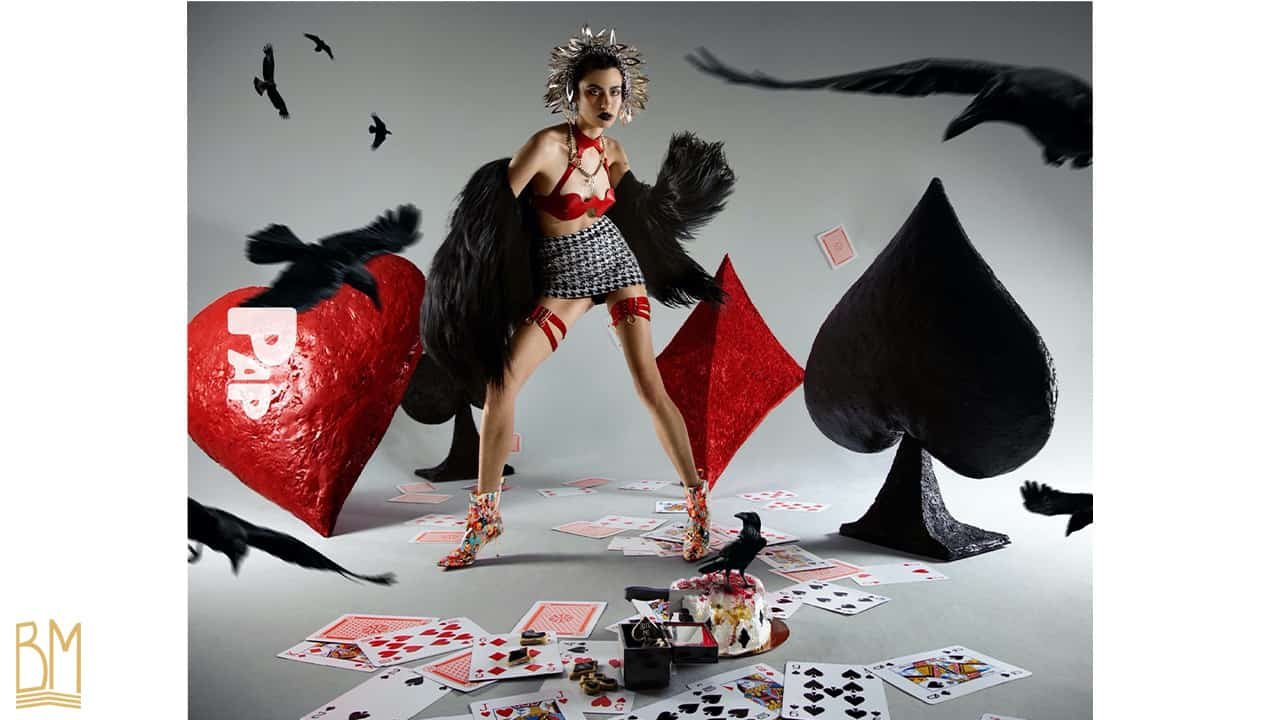 PAP Magazine femme portant un soutien-gorge Whiplash Cuir rouge ainsi que les jartelles rouges de la marque ELF ZHOU LONDON. Par dessus elle porte une veste noir à poil. Derrière elle, se trouve le signe du coeur, du trèfle, du pique et du carreau. On peut voir sur le sol des cartes éparpillés et un gâteau en partie mangé avec à côté un corbeau. D'autres corbeaux volent autour du modèle.