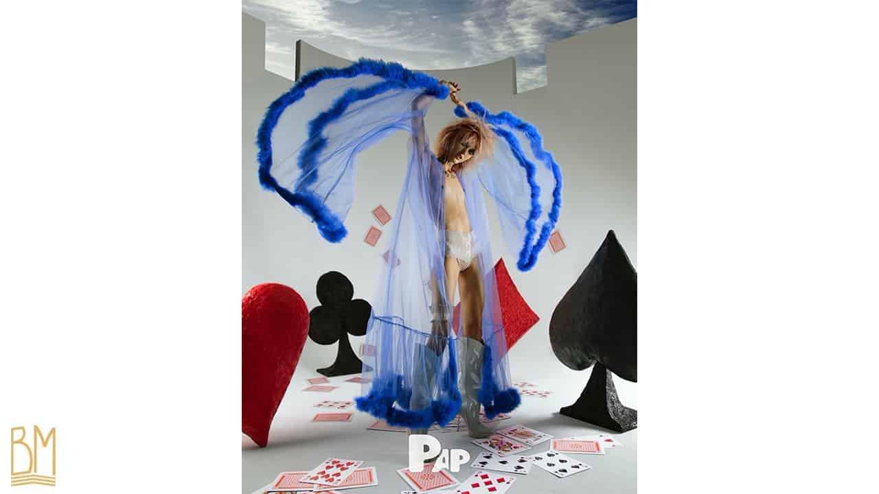 PAP Magazine Il s'agit d'une femme portant . Par dessus elle porte une culotte G-string de la marque Bracli. Derrière elle, se trouve le signe du coeur, du trèfle, du pique et du carreau. On peut voir sur le sol des cartes éparpillés et d'autres qui tombent.