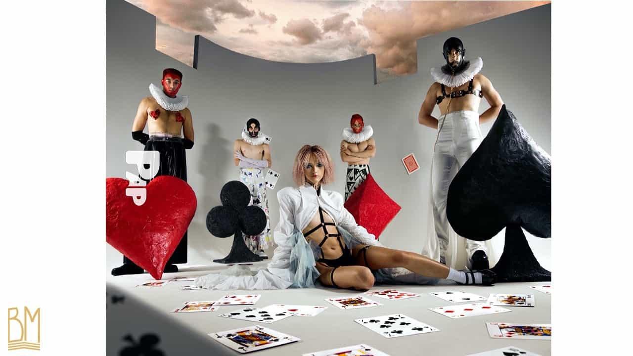 PAP Magazine il y a 4 hommes vêtus en noir, rouge et blanc positionnés autour d'une femme assise portant une cape blanche et un harnais noir. L'homme en rouge à gauche porte des Nippies de la marque Ruth Melbourne. L'homme à l'autre extrémité porte une laisse de la marque Upko. Devant chaque homme il y a un coeur rouge, un trèfle noir, un losange rouge, un pique noir. Sur le sol sont éparpillées des cartes.