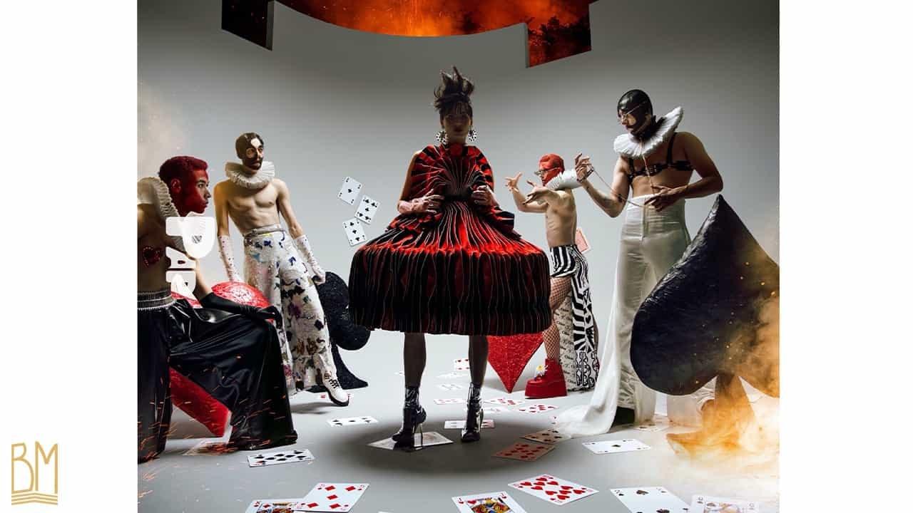 PAP Magazine il y a 4 hommes vêtus en noir, rouge et blanc positionnés autour d'une femme debout vêtue d'une robe rouge et noire. L'homme le plus à droite porte une laisse de la marque Upko. Devant chaque homme il y a un coeur rouge, un trèfle noir, un losange rouge, un pique noir. Sur le sol sont éparpillées des cartes.