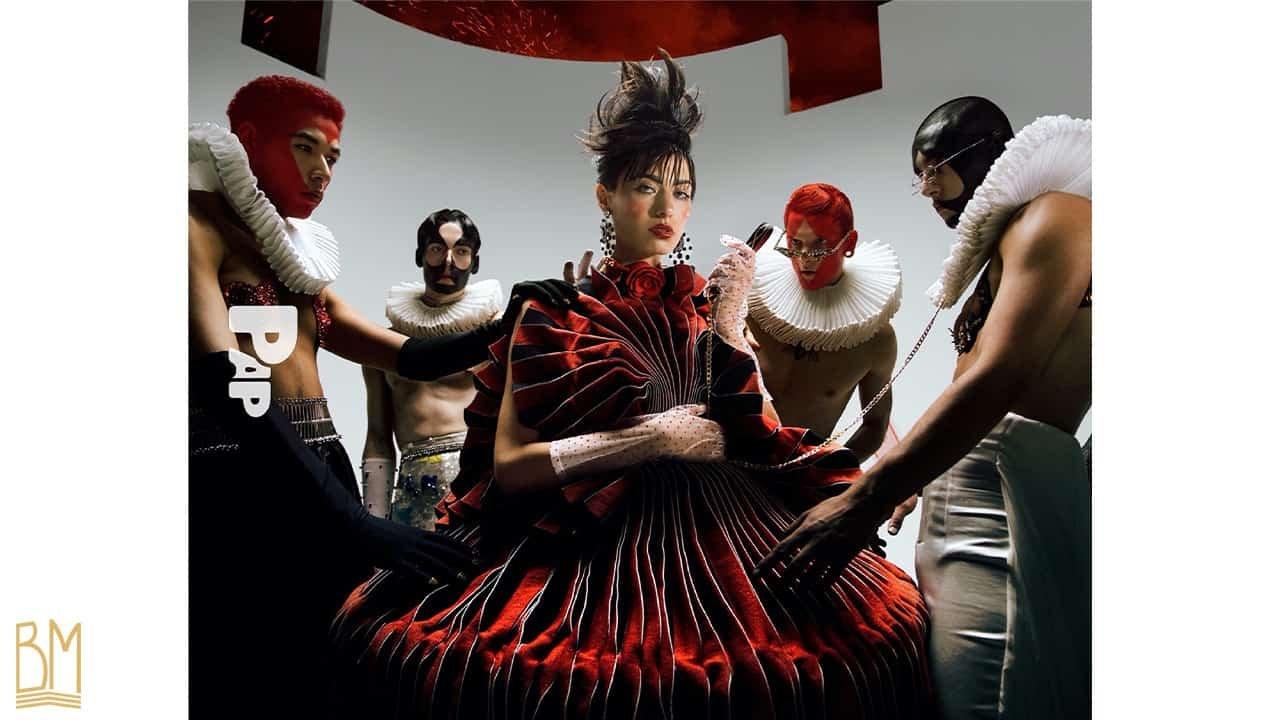 PAP Magazine il y a 4 hommes vêtus en noir, rouge et blanc positionnés autour d'une femme debout vêtue d'une robe rouge et noire. L'homme le plus à droite porte une laisse de la marque Upko. L'homme à l'autre extrémité porte des Nippies de la marque Ruth Melbourne.