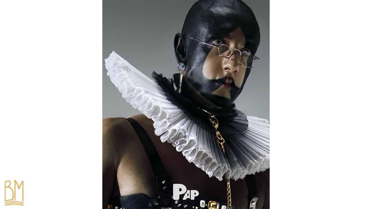 PAP Magazine il s'agit d'un homme portant une laisse de la marque Upko. Son visage est peint en noir et forme le signe du pique