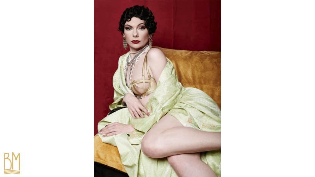 Julie Von Trash wears a golden Gonzales bra, and a pearl necklace