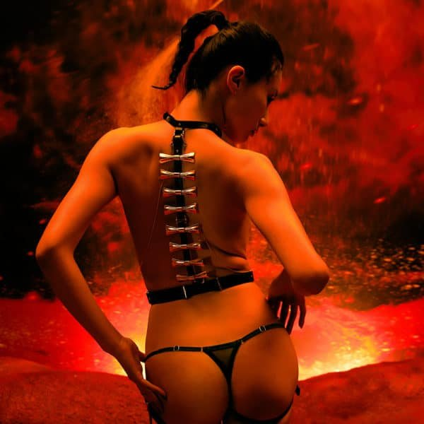Ensemble Bondage 8 pièces de la marque Upko noir et or. Le haut est noir et possède à l'arrière des noeuds couleur or qui descendent le long du dos. De part et d'autre, se trouvent des chaines couleur or qui relient le haut et le bas du harnais en diagonale. Le bas est un string noir. À l'arrière le fond est rouge, le décor est un volcan en éruption.