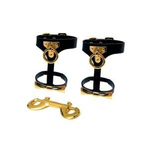Harnais Cheville Bondage de la marque Upko noir et or. En bas du harnais se trouve un noeud couleur or et haut une petite boucle en or. Est fourni avec un mousqueton en or.