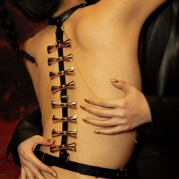 Ensemble Bondage 8 pièces de la marque Upko noir et or. Le haut est noir et possède à l'arrière des noeuds couleur or qui descendent le long du dos. De part et d'autre, se trouvent des chaines couleur or qui relient le haut et le bas du harnais en diagonale.